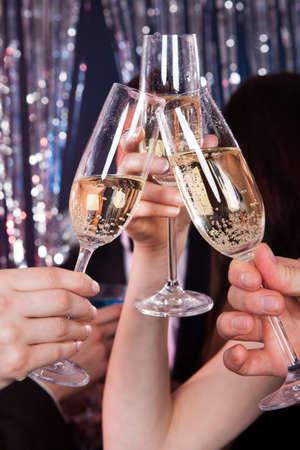 brindisi champagne: Immagine ritagliata di amici tostatura flauti champagne al nightclub