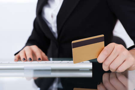 Midsection of businesswoman holding credit card at desk in office photo