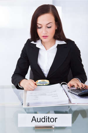 auditor: Young female auditor scrutinizing financial documents at desk in office Stock Photo