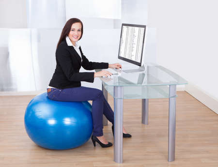 Side view portrait of businesswoman using computer while sitting on pilates ball in office Stock Photo