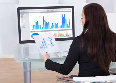 Rear view of businesswoman analyzing charts at desk in office photo