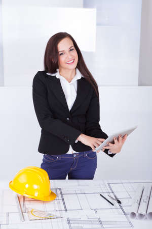 Portrait of smiling female architect with digital tablet standing at desk in office photo