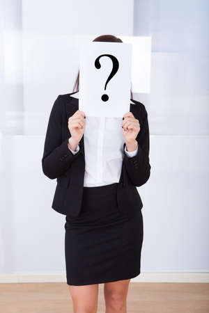 Young businesswoman holding question mark sign in front of her face at office photo