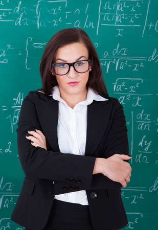 Portrait of confident young teacher standing arms crossed against chalkboard in classroom photo