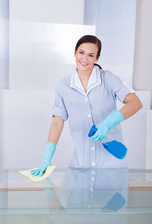 Portrait of happy young maid cleaning glass table at home photo