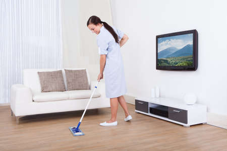 Full length portrait of young maid cleaning floor with mop at home photo