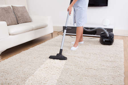vacuum cleaning: Cropped image of young maid cleaning carpet with vacuum cleaner at home Stock Photo