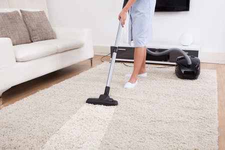 sirvienta: Imagen cosechada de la joven doncella de limpieza de alfombras con la aspiradora en casa