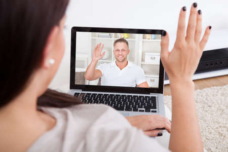 Cropped image of young woman using laptop for video conference at home photo