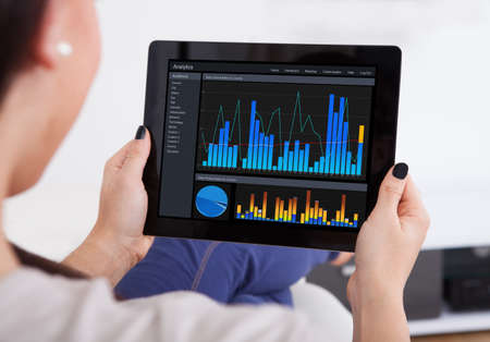 cropped image: Cropped image of young woman using analytics application on digital tablet