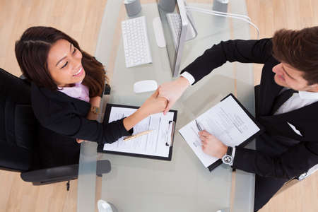 High angle view of business people shaking hands at desk in office