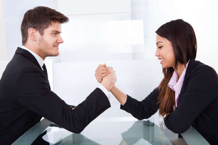 Side view of business colleagues arm wrestling at desk in office photo