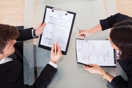 사무실에서 책상에 서류를 통해 논의하는 사업 사람들의 높은 각도보기 스톡 콘텐츠
