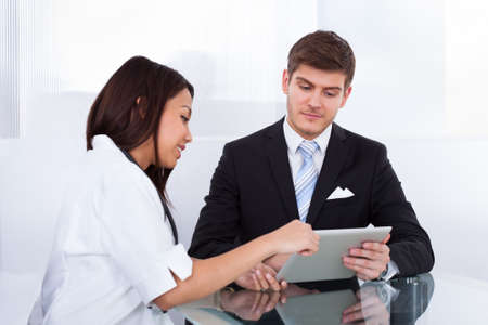 Side view of female doctor showing digital tablet to businessman in clinic photo