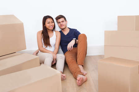 Portrait of young multiethnic couple sitting on floor at new home photo