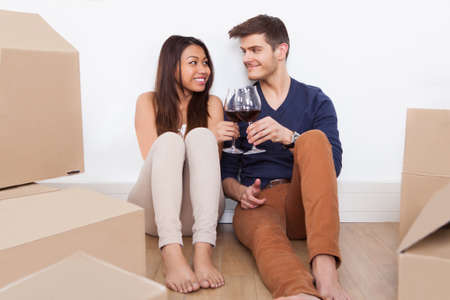 Loving young couple toasting wineglasses while sitting on floor in new home photo