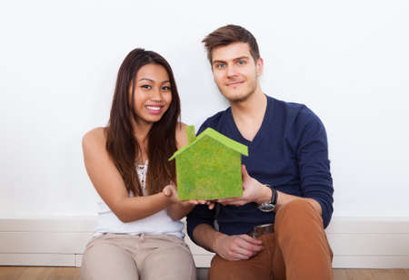 Portrait of young multiethnic couple holding green house model at new home photo