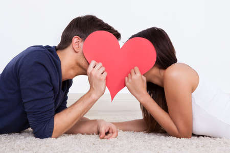 Side view of young couple hiding behind heart shape while lying on rug at home
