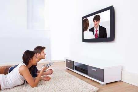 pareja viendo tv: Joven pareja viendo televisi�n mientras est� acostado en la alfombra en su casa