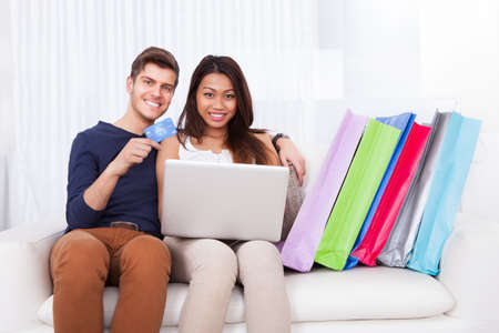 Portrait of happy young couple shopping online with bags on sofa at home photo
