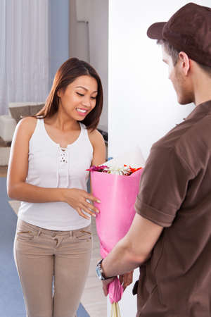 Happy young woman receiving flower bouquet from delivery man at home photo