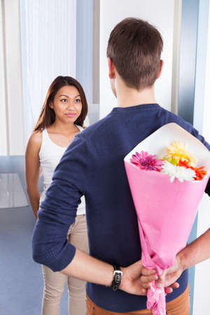 Rear view of young man hiding bouquet from woman at house doorway photo