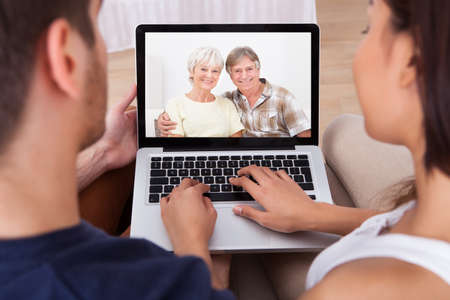 High angle view of young couple videocalling parents at home photo