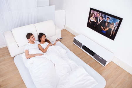 Young couple watching TV while lying in bed at home photo