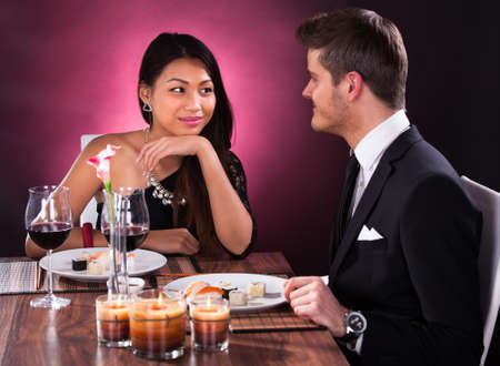 Loving couple looking at each other while having meal at restaurant table photo