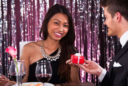 Portrait of happy young woman receiving gift from man in restaurant photo