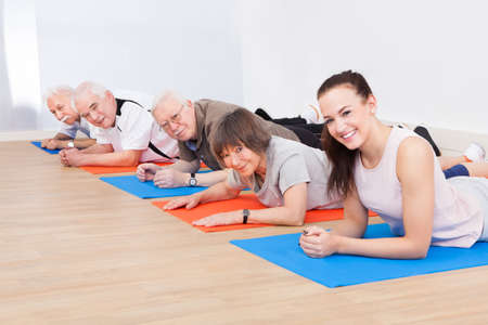 Portrait of smiling trainer and senior customers performing yoga on floor at gym photo