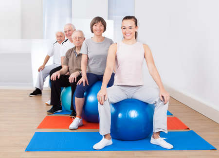 Portrait of smiling trainer and senior customers sitting on fitness balls in exercise class photo