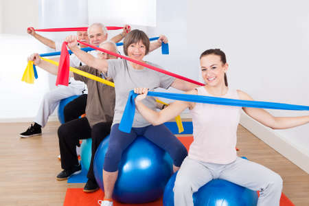elastic: Portrait of trainer and senior customers with resistance bands sitting on fitness balls at gym
