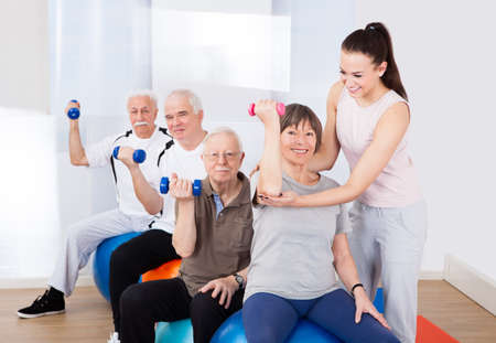 Young female trainer assisting senior people with dumbbells sitting on fitness balls at healthclub photo