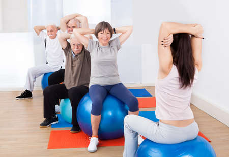 senior fitness: Rear view of female trainer training senior customers stretching on fitness balls in exercise class