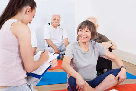 old people group: Young female trainer taking notes from senior customers at gym Stock Photo