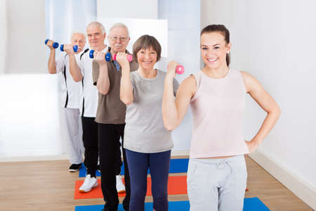 Portrait of happy trainer and senior customers exercising with dumbbells at gym photo
