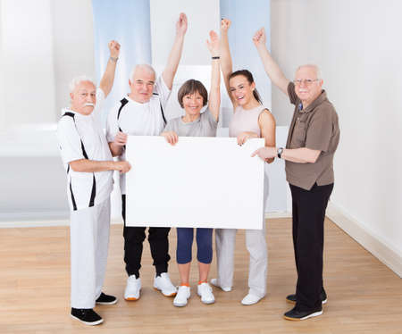 happy young man: Full length portrait of trainer and senior customers holding blank billboard at healthclub