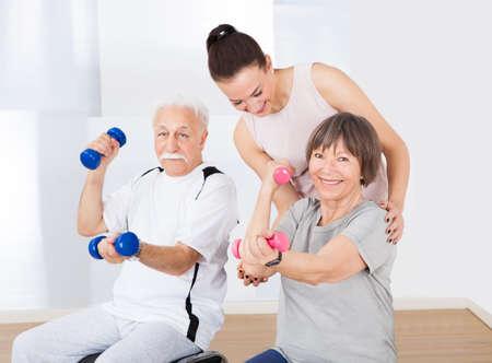 Jonge vrouwelijke trainer helpen senior paar met halters op healthclub