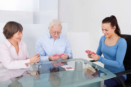 card game: Young female caretaker playing cards with senior couple at table in nursing home