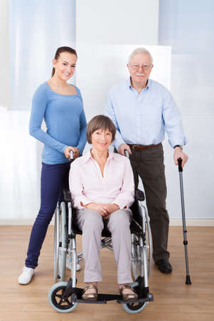 Portrait of female caregiver with disabled senior couple at nursing home photo