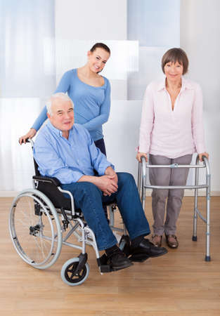 Portrait of disabled senior couple with female caregiver at nursing home photo