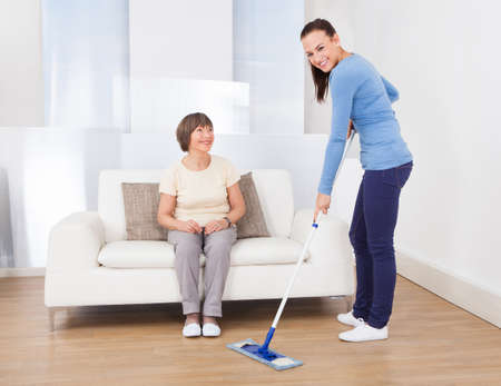 Portrait of caretaker cleaning floor with mop while senior woman sitting on sofa at nursing home photo