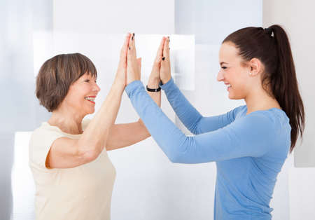 Side view of happy female caregiver and senior woman giving high five at nursing home