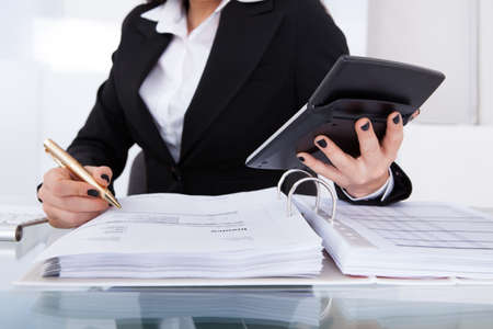 Midsection of female accountant calculating tax at desk in office photo