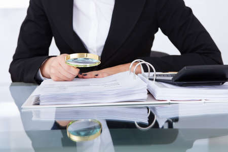 Closeup of uditor scrutinizing financial documents at desk in office Stock Photo