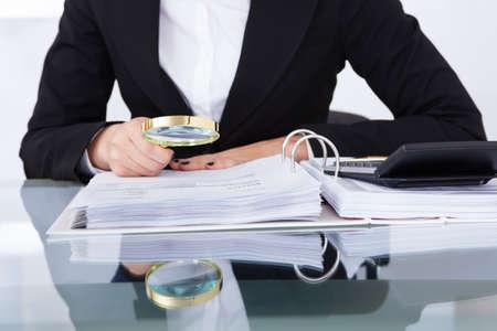 investigacion: Primer plano de uditor escrutando documentos financieros en el escritorio en la oficina Foto de archivo