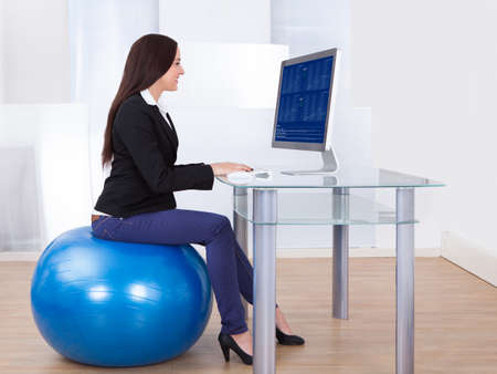 sitting at desk: Side view portrait of businesswoman using computer while sitting on pilates ball in office Stock Photo