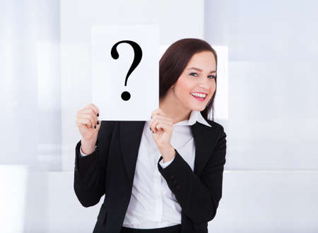 Portrait of happy young businesswoman holding question mark sign in office photo