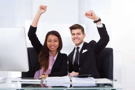 Portrait of successful accountants with hands raised sitting at desk in office photo